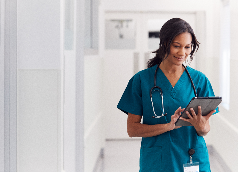 Healthcare worker holding digital tablet and stethoscope hanging from shoulders