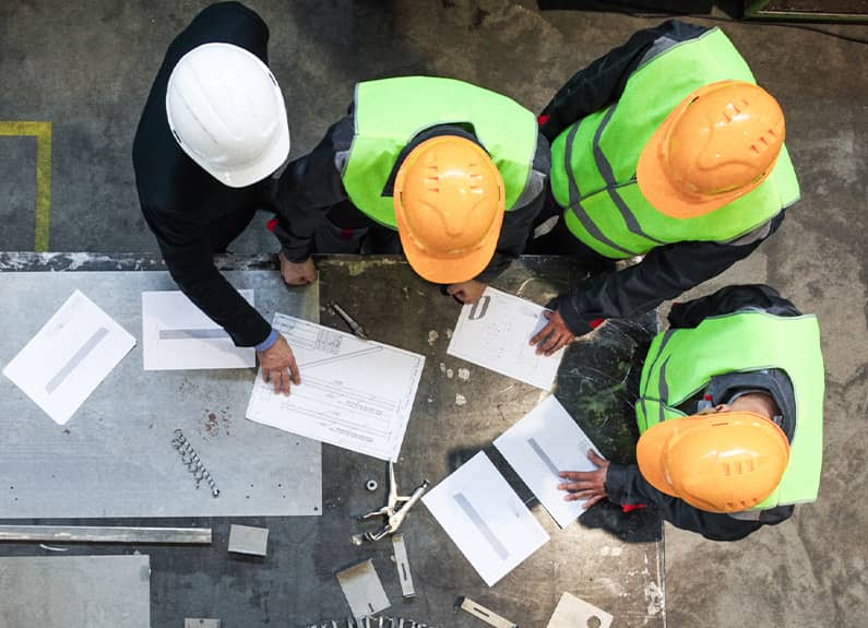 Group of workers on manufacturing floor wearing hard hats and reviewing design drafts at a metal table